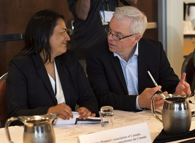 Michele Audette, left, from the Native Women's Association of Canada, chats with Manitoba Premier Greg Selinger at a meeting of premiers and aboriginal leaders in Charlottetown on Wednesday, August 27, 2014. THE CANADIAN PRESS/Andrew Vaughan