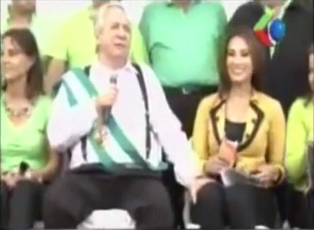 In this May 1, 2014 frame grab taken from APTN video provided by Giga Vision, Santa Cruz Mayor Percy Fernandez grabs the thigh of journalist Mercedes Guzman as he speaks during a public event in Santa Cruz, Bolivia. On Monday, May 5, 2014, Fernandez expressed
