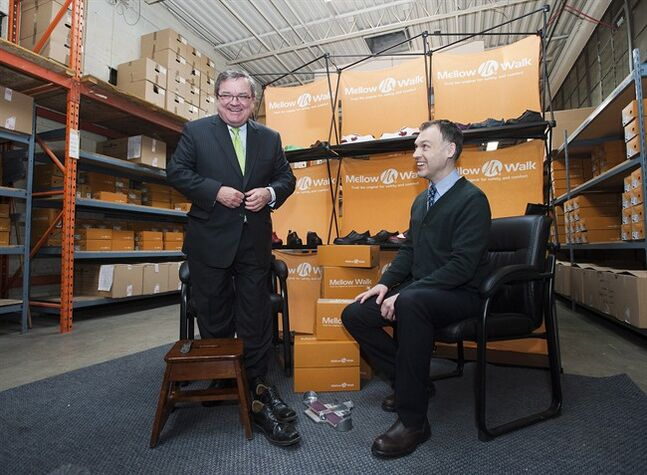 Finance Minister Jim Flaherty tries on a pair of shoes with Andrew Violi president of Mello Walk Shoes at a pre-budget press event in Toronto on Friday February 7, 2014. THE CANADIAN PRESS/Aaron Vincent Elkaim
