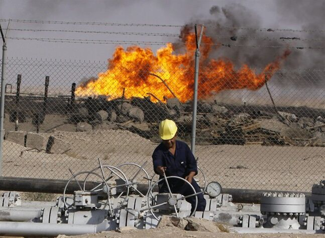 FILE - In this Dec. 13, 2009 file photo, an Iraqi worker operates valves at the Rumaila oil refinery near the city of Basra, 550 kilometers (340 miles) southeast of Baghdad, Iraq. The turmoil in Iraq has thrown the OPEC member's ambitious plans to boost oil production into doubt, threatening to crimp its most vital economic lifeline. Northern oil fields imperiled by the militants' advance have been shut down, and companies have begun evacuating workers elsewhere in the country. Iraq's Kurdish minority has moved to solidify control over the northern oil-rich city of Kirkuk and other disputed areas, weakening Baghdad's claims to the energy riches buried beneath while bolstering the Kurds' aspirations of greater autonomy. (AP Photo/Nabil al-Jurani, File)
