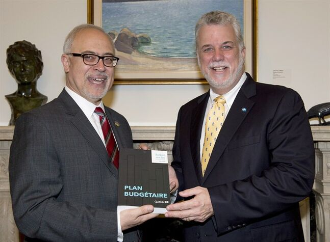 Quebec Premier Philippe Couillard, right, is handed a copy of the provincial budget by Finance Minister Carlos Leitao, Wednesday, June 4, 2014 at his office in Quebec City. The budget will be presented at the National Assembly later in the afternoon. THE CANADIAN PRESS/Jacques Boissinot
