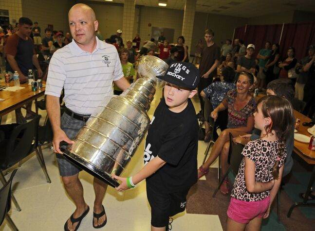 Darren Granger, along with his son Chase, carries the Stanley Cup into the Wheat Kings Hockey School barbeque, Thursday evening at the Keystone Centre. The trainer for the LA Kings had the Cup for a day and let the locals have a look.