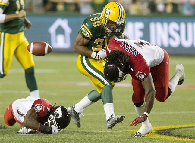Calgary Stampeders Lin-J Shell (1) knocks the ball lose from Edmonton Eskimos John White (30) and Joshua Bell (11) tries to tackleduring second half action in Edmonton, Alta., on Thursday July 24, 2014. THE CANADIAN PRESS/Jason Franson.