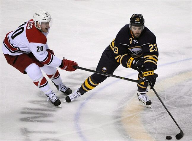 Carolina Hurricanes center Riley Nash (20) hooks Buffalo Sabres left winger Ville Leino (23), of Finland, during the third period of an NHL hockey game in Buffalo, N.Y., Tuesday, Feb. 25, 2014. THE CANADIAN PRESS/AP/Gary Wiepert