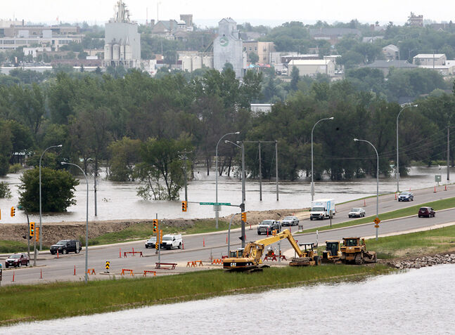 Equipment is situated at the dike along 18th Street near Kirkcaldy Avenue on Thursday. With the second Assiniboine River crest expected today, the city is reminding people to stay away from dikes and avoid 18th Street North whenever possible.
