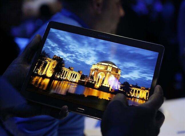 FILE - In this Thursday, June 12, 2014, file photo, a member of the media tries out a new Samsung Galaxy Tab S after the tablet's debut at a news conference in New York. The new display technology in Samsung's Galaxy Tab S tablet brings colors to life and reduces the device's bulk. (AP Photo/Kathy Willens, File)