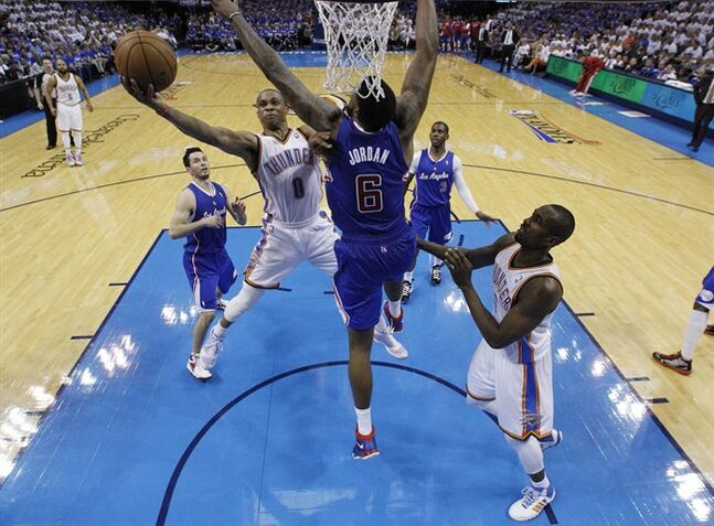 Oklahoma City Thunder guard Russell Westbrook (0) shoots in front of Los Angeles Clippers center DeAndre Jordan (6) in the second quarter of Game 2 of the Western Conference semifinal NBA basketball playoff series in Oklahoma City, Wednesday, May 7, 2014. Thunder forward Serge Ibaka (9) is at right. (AP Photo/Sue Ogrocki)