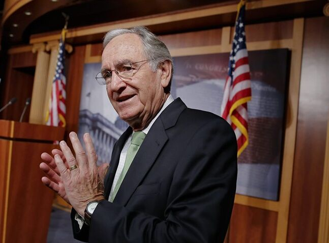 FILE - In this Nov. 7, 2013 file photo, Sen. Tom Harkin, D-Iowa speaks with reporters on Capitol Hill in Washington. Boosting the federal minimum wage as President Barack Obama and congressional Democrats are proposing would increase earnings for more than 16.5 million people by 2016 but also cut employment by roughly 500,000 workers, Congress' nonpartisan budget analyst said Tuesday. Harkin, author of the Senate legislation, cited other research concluding that a higher minimum wage would create jobs, not reduce them. (AP Photo/J. Scott Applewhite, File)