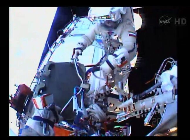 In an image made from NASA TV, the helmet camera of flight engineer Sergey Ryazanskiy shows commander Oleg Kotov Monday Jan. 27, 2014, as they install a Canadian-made high-resolution camera outside the International Space Station. Ryaazansky's gloved hand is at lower left. THE CANADIAN PRESS/AP, NASA
