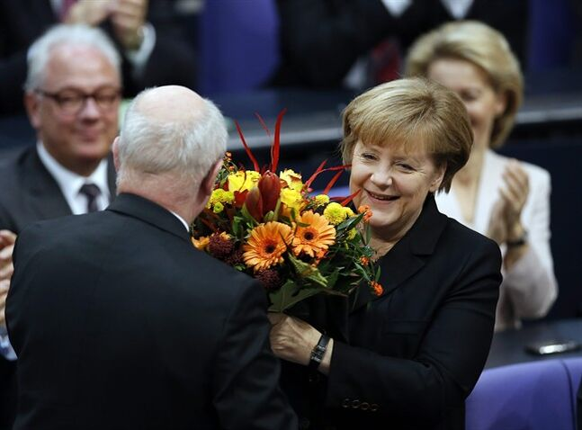 German Chancellor Angela Merkel receives flowers from well-wishers after being reelected during a meeting of the German federal parliament, Bundestag, in Berlin, Germany, Tuesday, Dec. 17, 2013. (AP Photo/Michael Sohn)
