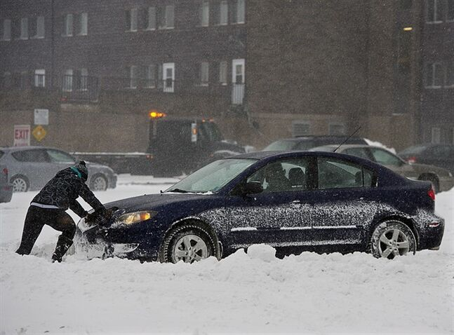 A passenger pushes a car in a parking lot in Halifax on Sunday, Dec.15, 2013. The storm is expected to dump up to 30 centimetres of snow on the region.THE CANADIAN PRESS/Andrew Vaughan