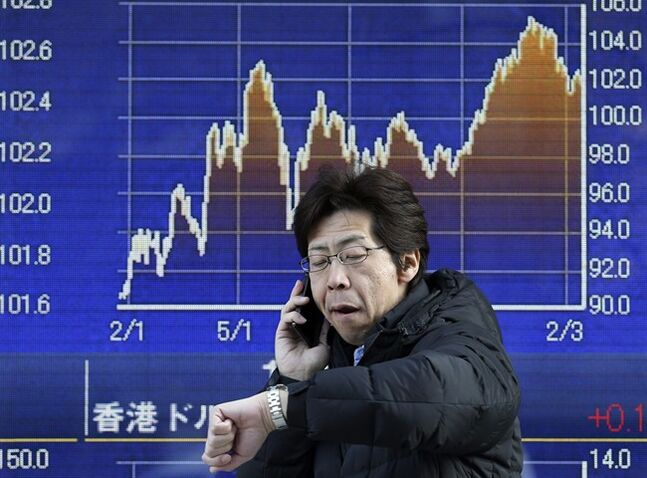 A man talks on the mobile phone in front of an electronic stock board of a securities firm in Tokyo, Tuesday, Feb. 18, 2014. Japan led Asian stock markets higher Tuesday after the country's central bank announced new measures to support growth.(AP Photo/Koji Sasahara)