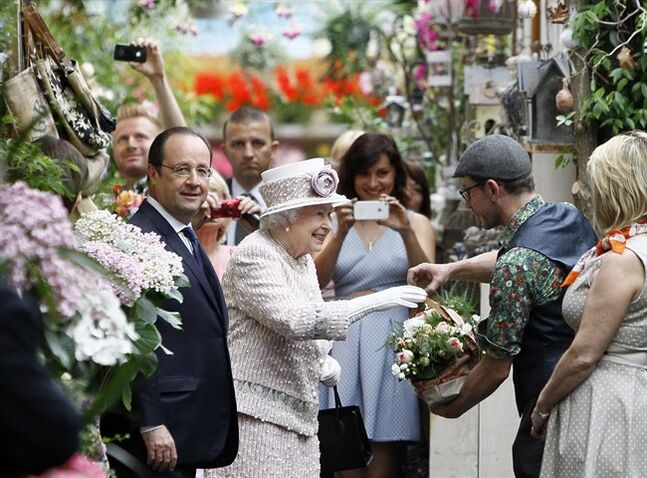 Britain's Queen Elizabeth II, centre, and French President Francois Hollande, left, receive flowers during a visit at the Flowers Market (Marche aux Fleurs) in Paris, Saturday, June 7, 2014. Queen Elizabeth finishes her three-day state visit in France following the international D-Day commemoration ceremonies in Normandy, marking the 70th anniversary of the World War II Allied landings in Normandy. (AP Photo/Francois Mori, Pool)