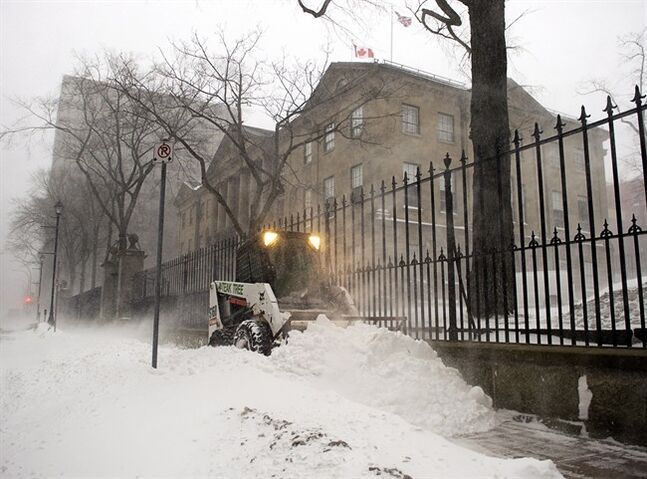A sidewalk plow works near the Nova Scotia legislature in blizzard conditions in Halifax on Friday, Jan. 3, 2014. THE CANADIAN PRESS/Andrew Vaughan