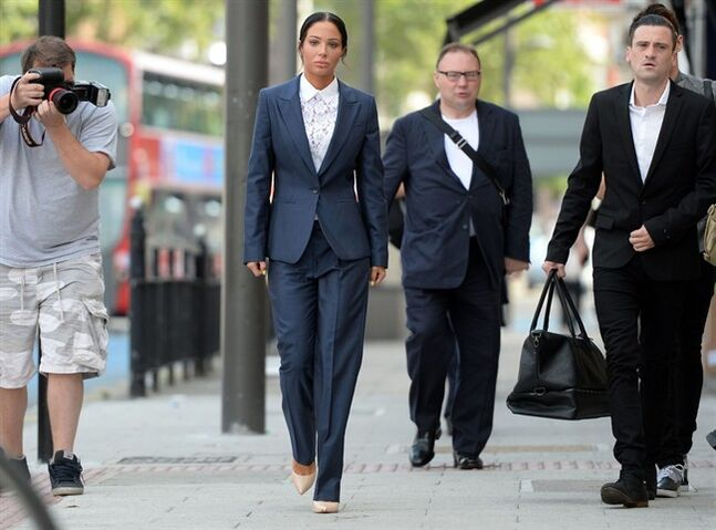 "British singer Tulisa Contostavlos, centre, arrives at Stratford Magistrates Court, in London, Friday July 25, 2014. British singer and former ""X Factor"" judge Tulisa Contostavlos, who last week won a legal victory over a tabloid sting story, has been fined for assaulting a celebrity blogger at a music festival. The 26-year-old celebrity was convicted Friday of hitting Savvas Morgan during an altercation at the V Festival in August 2013. A judge at Stratford Magistrates Court in London ordered her to pay a 200 pound ($340) fine plus almost 3,000 pounds ($5,100) in other costs. (AP Photo/PA, Anthony Devlin) UNITED KINGDOM OUT NO SALES NO ARCHIVE"