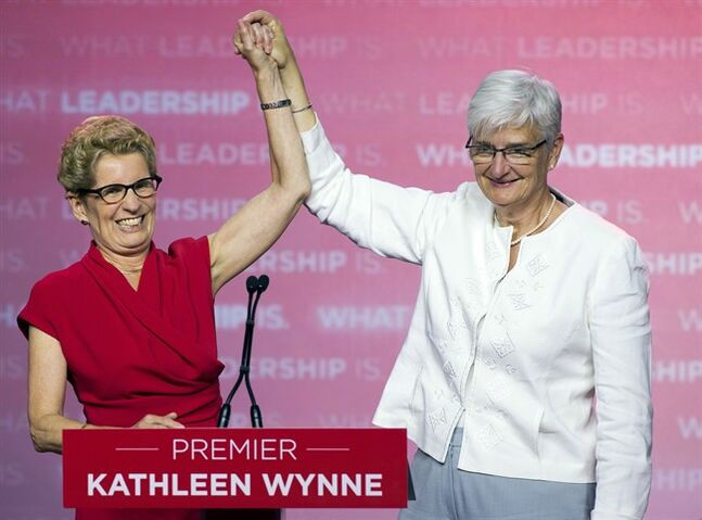 Ontario Premier Kathleen Wynne celebrates on stage with her partner Jane Rounthwaite after winning the provincial election in Toronto on Thursday June 12, 2014. THE CANADIAN PRESS/Frank Gunn