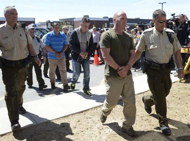 Former Montreal Maine and Atlantic Railway Ltd. employees Thomas Harding, right, Jean Demaitre, centre, and Richard Labrie are escorted by police to appear in court in Lac-Megantic, Que., on Tuesday, May 13, 2014. The Crown announced late Monday that Montreal Maine and Atlantic Railway Ltd. and three employees of the insolvent railway will each face 47 counts of criminal negligence causing death. THE CANADIAN PRESS/Ryan Remiorz