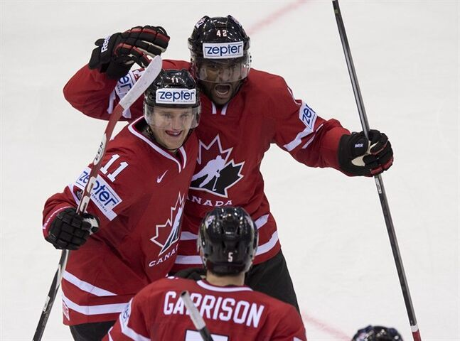 Canada's Joel Ward, top, celebrates with teammates Jonathan Huberdeau, left, and Jason Garrison after scoring against Slovakia during second period action at the IIHF Ice Hockey World Championship in Minsk, Belarus, on Saturday, May 10, 2014. THE CANADIAN PRESS/Jacques Boissinot