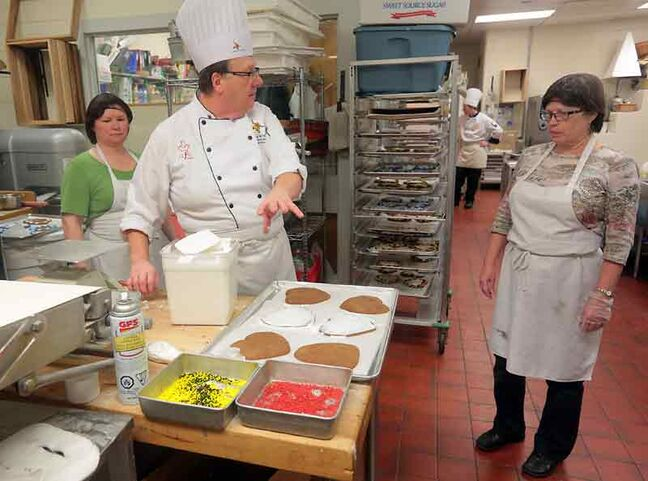 Crocus Plains culinary instructor Larry de Vries works with volunteers to prepare treats for the German pavilion in the kitchen at Crocus Plains high school on Friday afternoon.