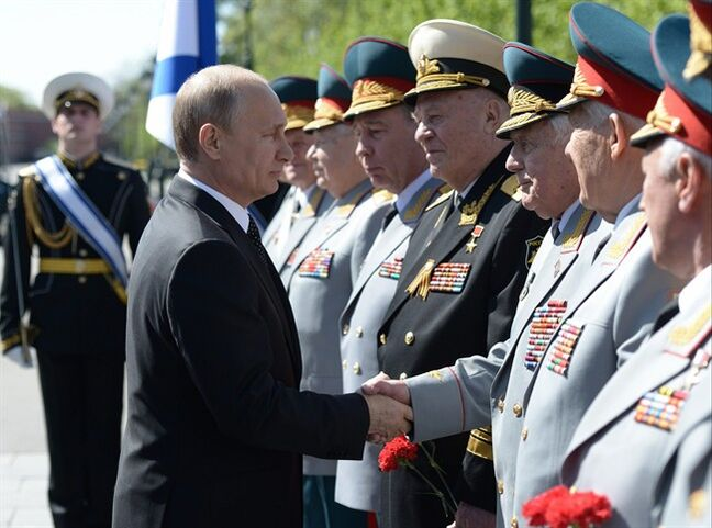 Russian President Vladimir Putin shakes hands with senior officers at a wreath laying ceremony at the Tomb of Unknown Soldier at the Kremlin wall on the eve of Victory Day marking the defeat of Nazi Germany 69 years ago in Moscow, Russia, on Thursday, May 8, 2014. Russia will mark Victory Day on May 9 holding a military parade in Red Square in Moscow. (AP Photo/RIA-Novosti, Alexei Nikolsky, Presidential Press Service)
