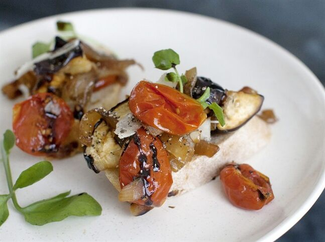 This July 21, 2014 photo shows tangy tomato-eggplant crostini in Concord, N.H. Salting and draining the eggplants and tomatoes removes excess water, which not only makes for a meatier texture, it also concentrates the flavors. (AP Photo/Matthew Mead)