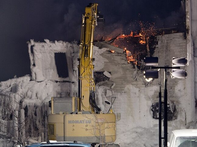 A crane knocks down a wall after a fatal fire destroyed a seniors residence in L'Isle-Verte, Que., Thursday, January 23, 2014. THE CANADIAN PRESS/Ryan Remiorz