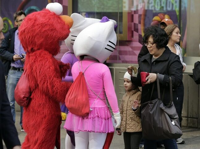 FILE - In this April 9, 2013 file photo, a woman prepares to pay characters in New York's Times Square after she photographed a young girl with them. A New York City Council member is drafting legislation to regulate the costumed characters who roam Times Square. The bill being proposed by Councilman Dan Garodnick would require that the costumed performers be licensed and go through a background check. There have been a number of troublesome incidents involving costumed figures who try to make a living by charming tourists. (AP Photo/Richard Drew, File)