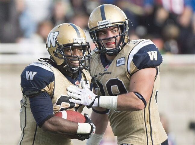 Winnipeg Blue Bombers' Will Ford, left, celebrates with teammate Michel-Pierre Pontbriand after scoring a touchdown against the Montreal Alouettes during second half CFL football action in Montreal, Monday, October 14, 2013. The Bombers have signed Canadian fullback Pontbriand to a new contract.THE CANADIAN PRESS/Graham Hughes