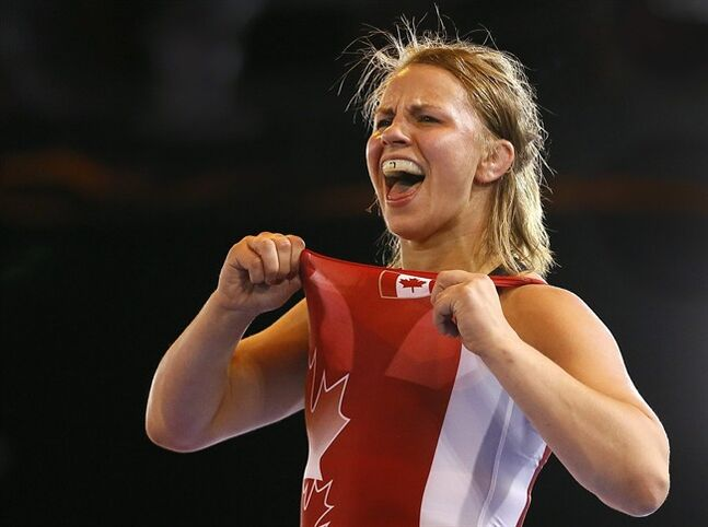 Erica Wiebe of Canada celebrates winning gold in a bout against Jyoti of India in the Nordic System 75kg wrestling bout at the Scottish Exhibition Conference Centre during the Commonwealth Games 2014 in Glasgow, Scotland, Tuesday July 29, 2014. (AP Photo/Kirsty Wigglesworth)