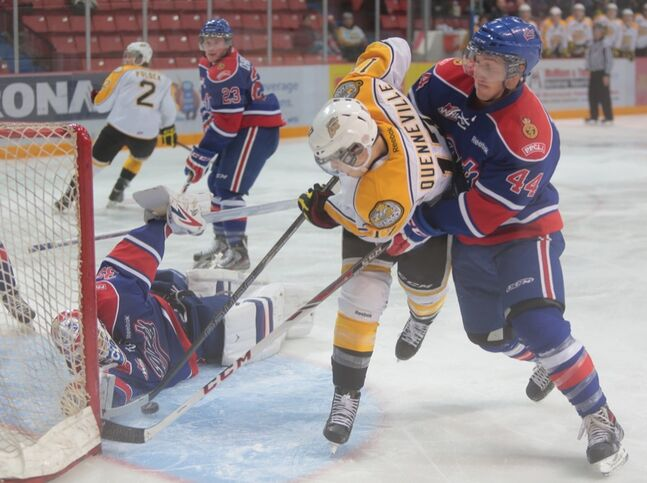 Wheat Kings John Quinneville tried to sneak the puck under Regina Pats' goaltender Nick Schneider as Jesse Zqraggen ties him up during Friday night's WHL game at Westman Place.
