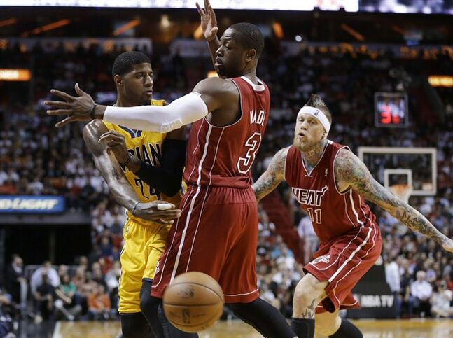 Indiana Pacers' Paul George (24) passes the ball as Miami Heat's Dwyane Wade (3) defends in the first half of an NBA basketball game, Wednesday, Dec. 18, 2013, in Miami. At right is Chris Andersen (11). (AP Photo/Lynne Sladky)