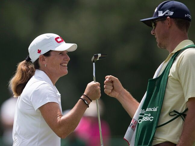 Lorie Kane celebrates a birdie with her caddy on the 8th green during the fourth round of the Manulife Financial LPGA Classic in Waterloo, Ont., on July 14, 2013. Lorie Kane has played in 21 Canadian Women's Opens. Now she's eager to promote it to sell tickets for next week's event in London, Ont., for the sake of charity and quality golf. THE CANADIAN PRESS/ Geoff Robins