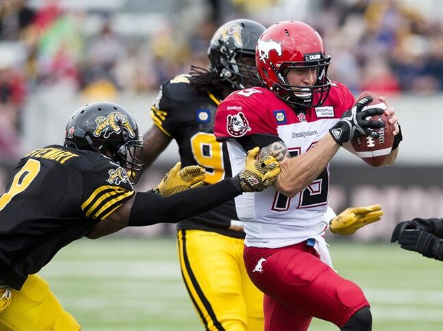 Calgary Stampeders quarterback Bo Levi Mitchell, right, run in for a touch down past Hamilton Tiger-Cats defensive back Brandon Stewart, left, during first half CFL football action in Hamilton, Ont., on Saturday, August 16, 2014. THE CANADIAN PRESS/Nathan Denette