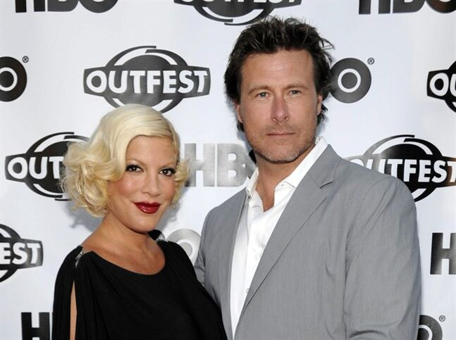 FILE - In this July 7, 2011 file photo, actress Tori Spelling, left, and actor Dean McDermott arrive at the premiere of the feature film