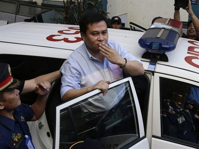 Philippine Senator Jinggoy Estrada blows a kiss as he is whisked to his detention cell after surrendering to police authorities Monday, June 23, 2014 at Philippine National Police headquarters at suburban Quezon city, northeast of Manila, Philippines. Estrada, the son of former President Joseph Estrada, surrendered Monday after a court ordered his arrest on corruption charges, the second celebrity politician in days to end up in jail allegedly for plundering this poor Southeast Asian nation's coffers. (AP Photo/Bullit Marquez)