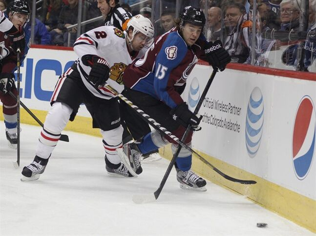 Chicago Blackhawks defenseman Duncan Keith, left, checks Colorado Avalanche right wing PA Parenteau off the puck in the first period of an NHL hockey game in Denver, Friday, March 8, 2013. (AP Photo/David Zalubowski)