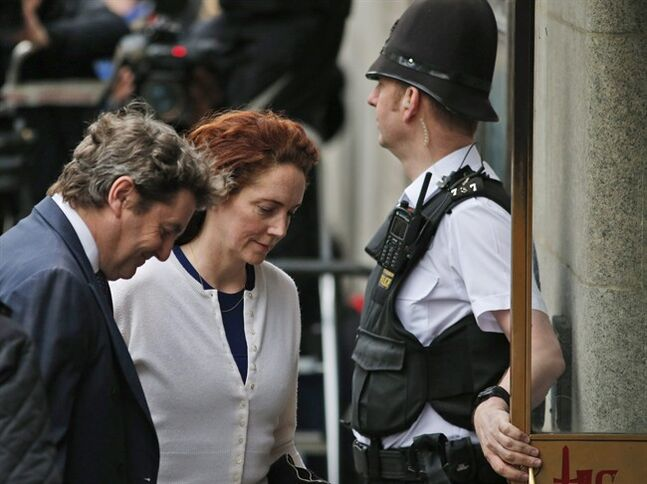 Rebekah Brooks, centre, former News International chief executive, and her husband Charlie Brooks, left, arrive at the Central Criminal Court in London where she appears to face charges related to phone hacking, Thursday, Feb. 20, 2014. (AP Photo/Lefteris Pitarakis)