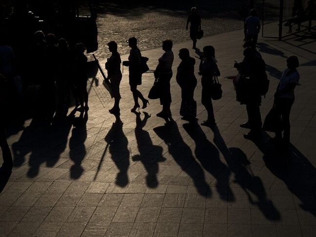 People cast shadows on the pavement while waiting for a bus during an outdoor memorial concert for victims of the Malaysian Airlines Flight 17 air crash in downtown Kharkiv, Ukraine, Thursday, July 24, 2014. Two military aircraft carrying remains of victims from the Malaysian plane disaster departed for the Netherlands on July 24, while Australian and Dutch diplomats joined to promote a plan for a U.N. team to secure the crash scene which has been controlled by pro-Russian rebels.(AP Photo/Vadim Ghirda)