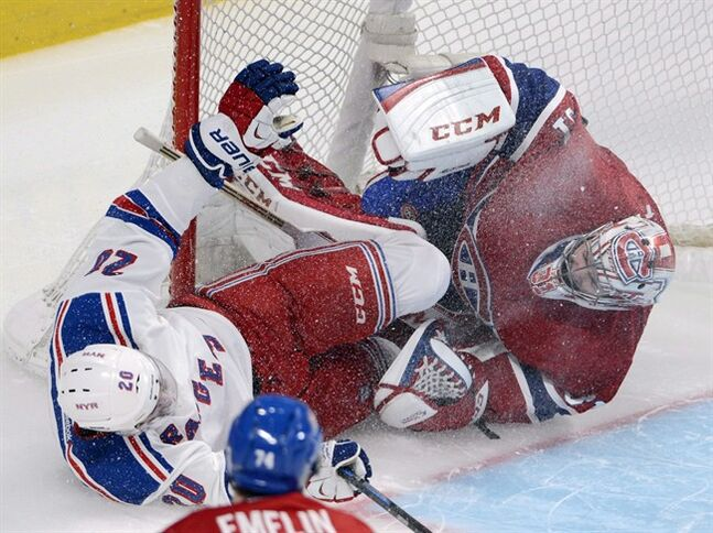New York Rangers Chris Kreider crashes into Montreal Canadiens goalie Carey Price, on May 17, 2014 in Montreal. THE CANADIAN PRESS/Ryan Remiorz