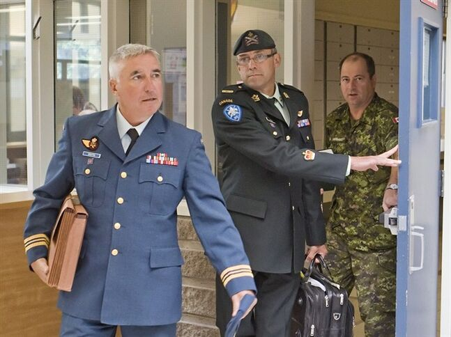 Warrant officer Andre Gagnon, centre, walks to testify at his court martial at the St-Malo Armoury Tuesday, August 12, 2014 in Quebec City with his defence counsel Major Philippe-Luc Boutin, left. THE CANADIAN PRESS/Clement Allard