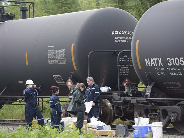 Investigators look over tanker cars pulled from the Lac-Megantic in Nantes, Que. on July 11, 2013. THE CANADIAN PRESS/Ryan Remiorz