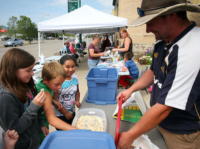 Andrew Maxwell gives out shortbread samples at the Mid-West Arts Council Farmer's Market in Hamiota.