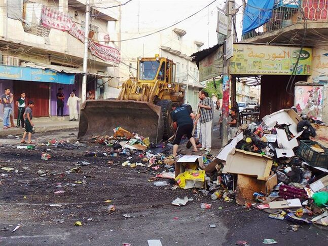 A municipality bulldozer and people clean up trash from a street in the northern city of Mosul, Iraq, Friday, June 13, 2014. Iraqi officials say al-Qaida-inspired militants who this week seized much of the country's Sunni heartland have pushed into an ethnically mixed province northeast of Baghdad, capturing two towns there.(AP Photo)