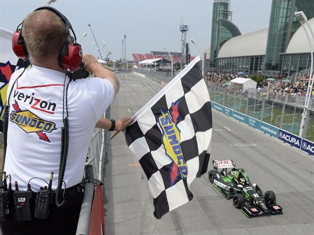 France's Sebastien Bourdais takes the checkeed flag to win the Toronto Indy race in Toronto on Sunday July 20, 2014. The race is the first race of a planned doubleheader.THE CANADIAN PRESS/Frank Gunn