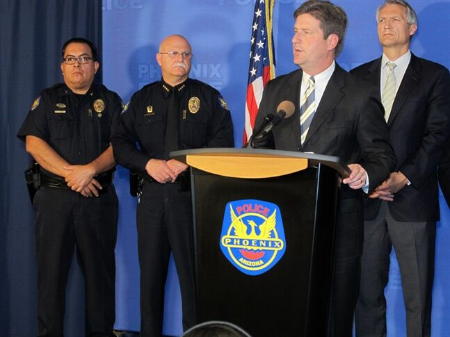 Phoenix Mayor Greg Stanton, second from right, speaks at a news conference announcing an arrest on Monday, June 16, 2014. Gary Michael Moran, 54, an ex-convict is being held for an attack that left one priest dead and another injured at a Roman Catholic church in Phoenix, connecting forensic evidence from the crime scene with the suspect. (AP Photo/Brian Skoloff)
