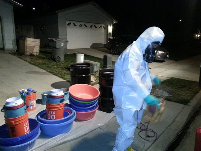 In this March 2014 photo provided by PARC Environmental, Jeff Davis, a hazardous materials specialist for PARC Environmental, cleans up a meth conversion lab inside a house in Madera, Calif. Authorities in California's Central Valley say that in recent years they have begun to see more meth dissolved as liquid and put into tequila bottles or plastic detergent containers to smuggle it across the border from Mexico. Once in the Central Valley, it is converted into crystals, it's most sought-after form on the street. In the seedy underworld of methamphetamine, traffickers have turned to disguising the drug as a liquid to boost chances of smuggling it into the United States from Mexico without getting caught.(AP Photo/PARC Environmental)