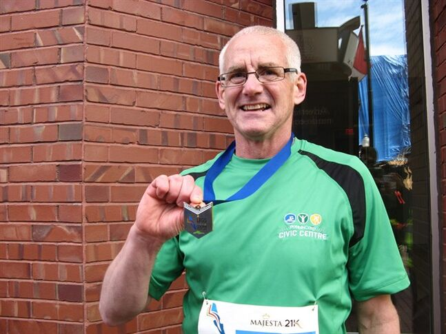 Dave Mulford of Sussex, N.B. displays his medal for finishing the Legs for Literacy marathon in Moncton, N.B. Sunday, May 4, 2014. Mulford began the race when it was held last October, but suffered a cardiac arrest just 600 metres from the finish line. He said he wanted to finish and thank the people who saved his life. THE CANADIAN PRESS/Kevin Bissett