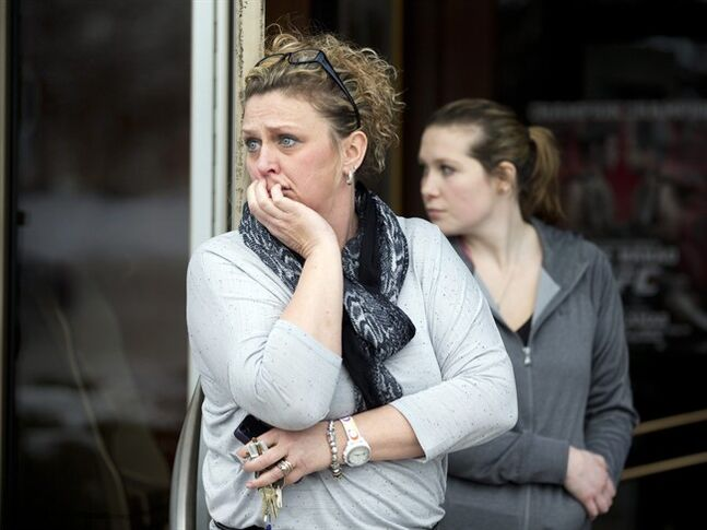 Restaurant general manager Heather Saffield and employee Chelsea Borschart, right, look outside their restaurant at The Mall in Columbia Saturday, Jan. 25, 2014, in Columbia, Md., Police continue the evacuation of the remaining mall visitors following a shooting that police say three people died including the presumed gunman. (AP Photo/Manuel Balce Ceneta)