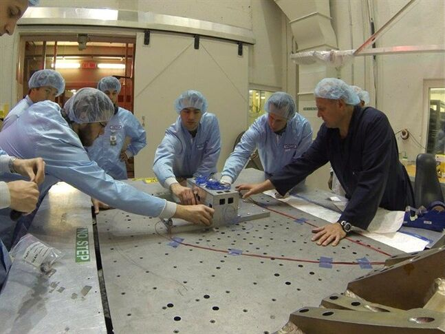 University of Victoria students, who won a contest involving universities across Canada, work on a small satellite in a handout photo. THE CANADIAN PRESS/HO
