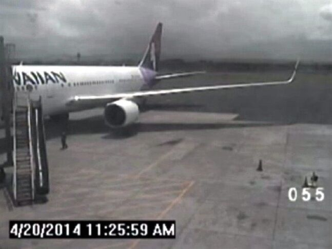 This April 20, 2014 image taken from a surveillance video provided by the Hawaii Department of Transportation, shows a California teen, left, after hopping from a jet's wheel well in Maui, Hawaii. Police said Tuesday, May 6, that they plan to interview the teen who stowed away on a Hawaii-bound flight two weeks ago, surviving sub-freezing temperatures as it crossed the Pacific Ocean. (AP Photo/Hawaii Department of Transportation)